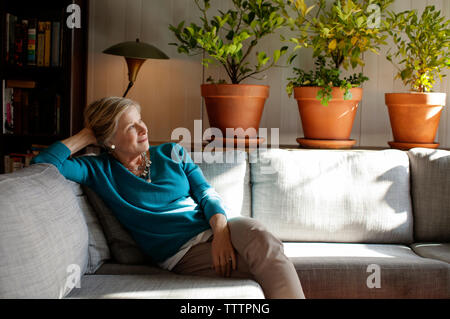 Thoughtful woman sitting on sofa at home - Stock Photo