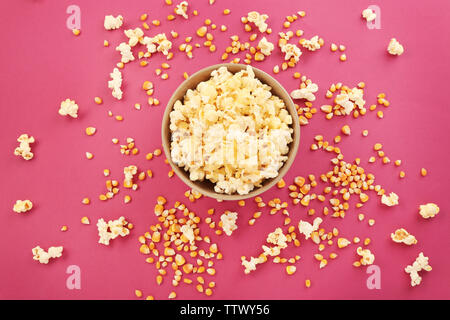 Bowl full of traditional popcorn on pink background - Stock Photo