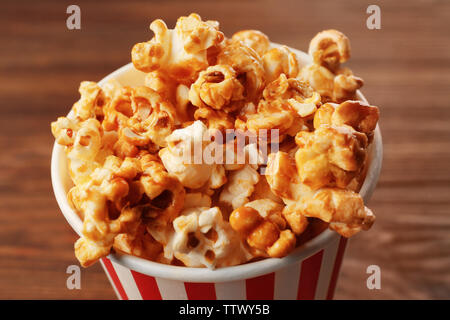 Caramel popcorn in striped box on wooden background - Stock Photo