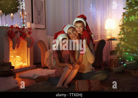 Young woman with Children opening Christmas present in living room - Stock Photo