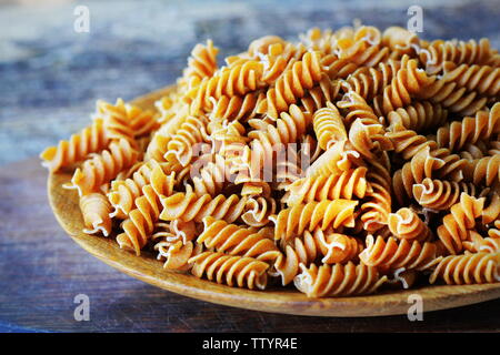 Wholemeal Fusilli in a plate. Integral Pasta over a wooden table - Stock Photo