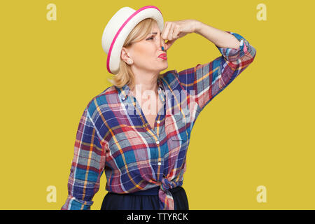 Portrait of disgusted modern stylish mature woman in casual style with white hat standing and pinching her nose because bad smell feeling and ignoring - Stock Photo