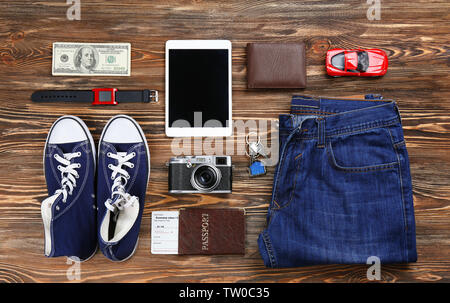 Flat lay of traveller's accessories on wooden background - Stock Photo