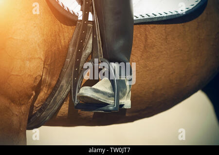 The leg of the rider, who sits on a Bay horse, in a black vintage dirty boot rests on the stirrup and is illuminated by bright sunlight. - Stock Photo