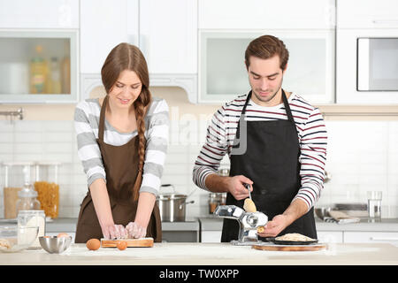 Young couple preparing pasta on kitchen table - Stock Photo