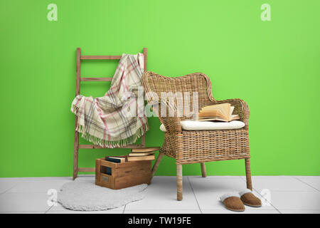 Wicker armchair and decorative ladder with plaid on green wall background - Stock Photo