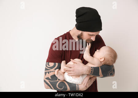 Handsome tattooed young man holding cute little baby on light background - Stock Photo
