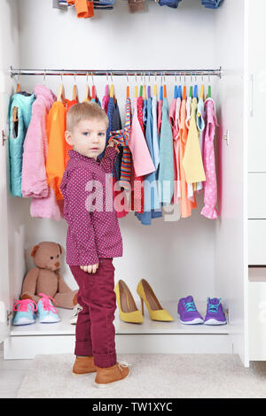 Cute small boy choosing clothes in wardrobe - Stock Photo