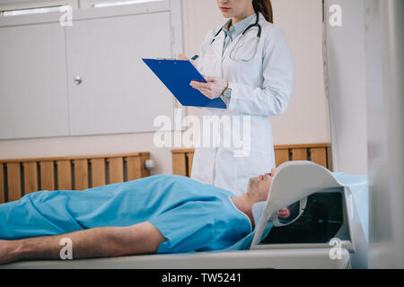 cropped view of young radiologist writing on clipboard while standing near patient lying on mri scanner bed - Stock Photo