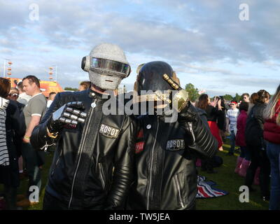 Newport, Isle of Wight. June 16 2019. Isle of Wight Festival - Human Robots duo with biker helmets showing off their attire nouveau costumes. - Stock Photo