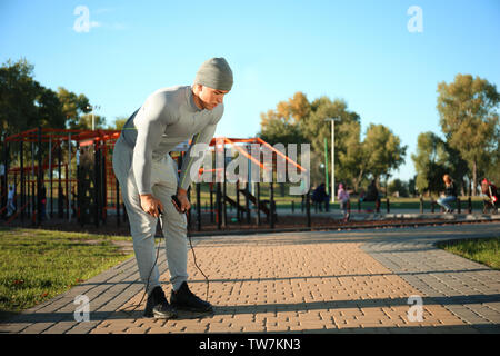 Sporty young man resting after jumping rope in park - Stock Photo