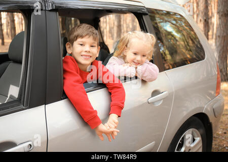 Adorable little children leaning out of car window - Stock Photo