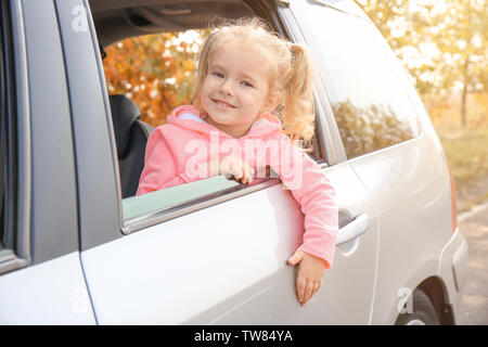 Adorable little girl looking out of car window - Stock Photo