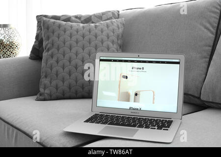 KYIV, UKRAINE - OCTOBER 18, 2017: MacBook Air Silver with Apple home page on sofa indoors - Stock Photo
