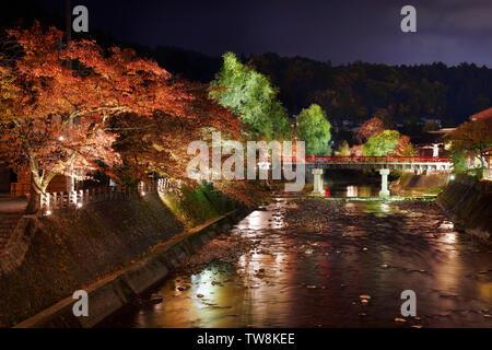 Nighttime autumn scenery of Miyagawa river in Takayama city with illuminated colorful red and green trees along the banks and red Nakahashi bridge - Stock Photo