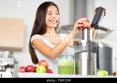 Juicing - woman making apple and green vegetable juice using juicer machine at home in kitchen. Healthy eating happy woman making green vegetable and fruit juice. Mixed race Asian Caucasian model. - Stock Photo
