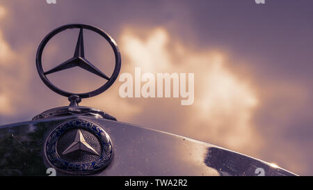BERLIN, GERMANY - MAY 19, 2019: Classic Mercedes Logo And Star On A Mercedes Vintage Car Against A Cloudy Sky - Stock Photo