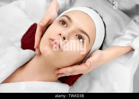 View from above of charming female lying on coach and relaxing while getting rejuvenative massage in salon. Professional doctor doing cosmetic procedures. Concept of beauty and care. - Stock Photo