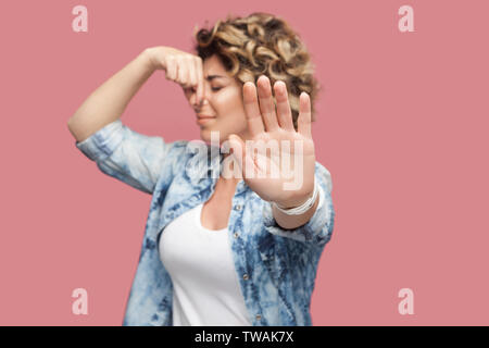 Bad smell blocking. Portrait of dissatisfied young woman with curly hair in casual shirt standing showing stop sign and pinching her nose with confuse - Stock Photo