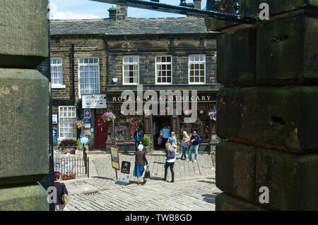 Tourists enjoying a summer's day in the village of Haworth in West Yorkshire UK, famous as the home of the Bronte sisters - Stock Photo