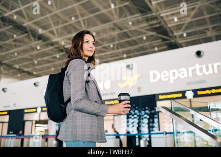 Young attractive traveler girl with backpack and coffee cup turning around at the departure zone at the airport. Travel vibes. - Stock Photo