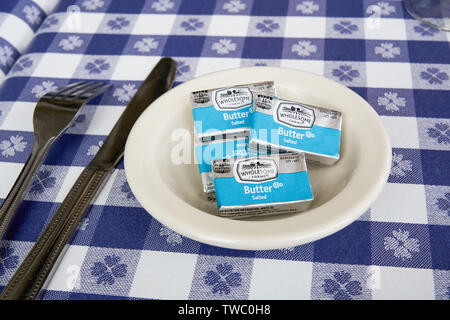 Hyannis, MA - June 10, 2019: Wrapped pats of Wholesome Farms salted butter in a dish on a blue and white check tablecloth with a fork and knife. Whole - Stock Photo