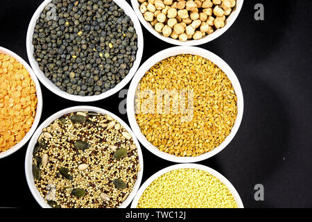 Healthy Selection of Mixed Seeds Sunflower Chia Linseed Couscous Chickpeas Red Green Lentils in White Bowls - Stock Photo