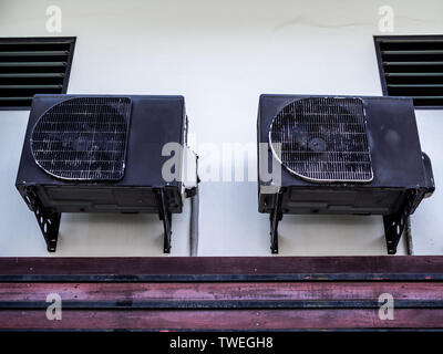 Two old black air conditioner compressors on white wall outside the house. - Stock Photo