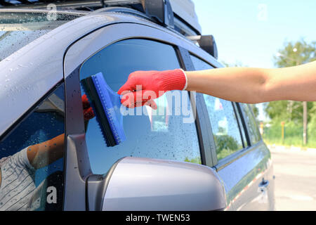 A man with a rubber scraper removes the remains of water from the glass after washing the car. Car wash. Self-service washing complex. High pressure c - Stock Photo