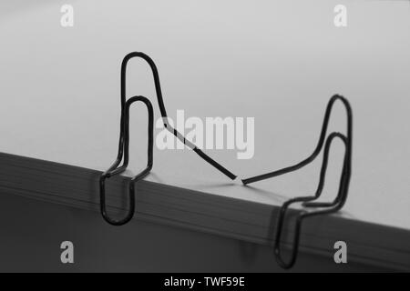 paper clips with heart symbolizing a person sitting on a stack of white paper. love concept - Stock Photo