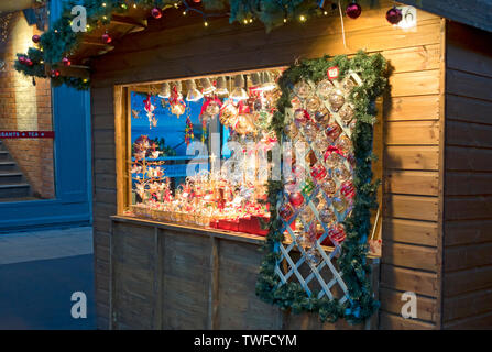 Christmas cabin selling decorations at St Nicholas Fayre. - Stock Photo