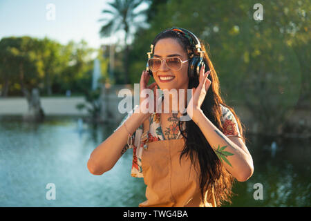 transgender model wearing sunglasses in the green park - Stock Photo