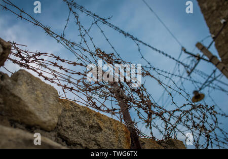 Old rusty barbed wire on the dark sky background. Selective focus. - Stock Photo