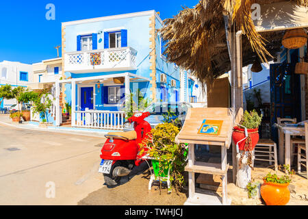 FINIKI PORT, KARPATHOS ISLAND - SEP 25, 2018: Vespa scooter in front of typical Greek tavern in Finiki port on Karpathos island. Greece is very popula - Stock Photo