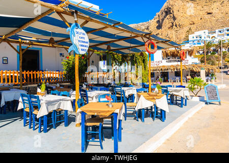 FINIKI PORT, KARPATHOS ISLAND - SEP 25, 2018: Typical Greek tavern in Finiki port on Karpathos island. Greece is very popular holiday destination in E - Stock Photo