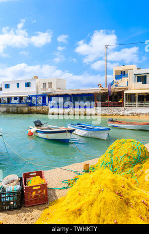Fishing boats in Lefkos port with tavernas in background, Karpathos island, Greece - Stock Photo