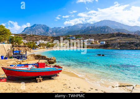 LEFKOS PORT, KARPATHOS ISLAND - SEP 29, 2018: Fisherman repairing boats on beautiful beach in Lefkos village on coast of Karpathos island, Greece. - Stock Photo