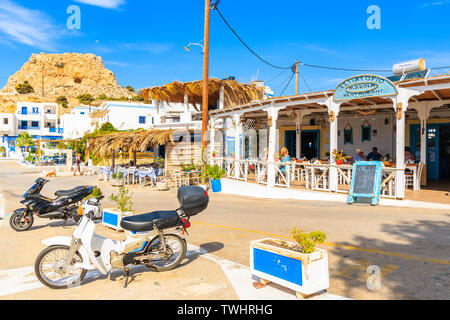 FINIKI PORT, KARPATHOS ISLAND - SEP 30, 2018: Scooters parking in front of typical Greek tavern on street of Finiki port, Karpathos island, Greece. - Stock Photo