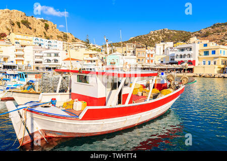 Fishing boats in Pigadia port on Karpathos island at sunset time, Greece - Stock Photo
