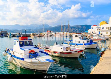 Fishing boats in Pigadia port on Karpathos island at sunset time, Greece - Stock Photo