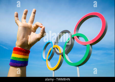 LONDON - MAY 4, 2019: A hand wearing gay pride rainbow colored wristband makes an OK gesture in front of Olympic Rings standing under bright blue sky. - Stock Photo