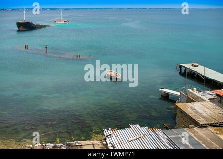Sunken ship near old abandoned docks on the shore. - Stock Photo
