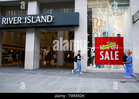 Shoppers walk past the River Island shop on Oxford Street as summer sales begin. Many departmental stores are offering huge discounts as they face competition from online shopping. - Stock Photo
