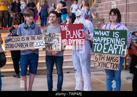 Liverpool, UK. June 22, 2019. Protesters from climate change group, Extinction Rebellion, hold a 'die-in' protest at Liverpool's Anglican Cathedral underneath Gaia, an art installation consisting of a 23ft replica of the Earth. Protesters laid down under the installation for 25 minutes which aimed to highlight lack of action on climate change. Credit: Christopher Middleton/Alamy Live News - Stock Photo