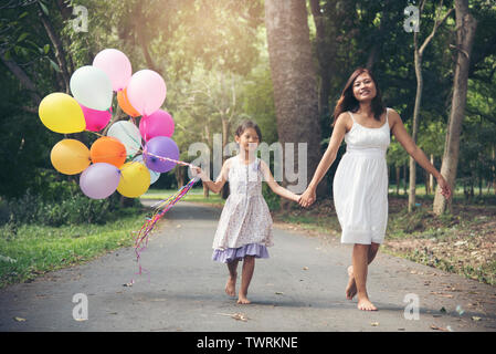 I love mom stay together on mother 's day.Adorable cute girl holding balloons with mother walking on the road in the park. Family Concept. - Stock Photo