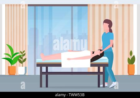 woman lying on massage bed african american masseuse doing healing treatment massaging injured patient manual physical therapy rehabilitation concept - Stock Photo