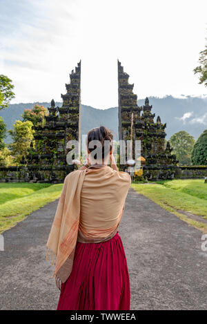 Unidentified woman at the traditional gate in Bali Indonesia. - Stock Photo