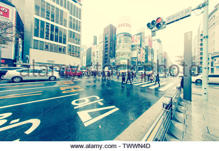 Tokyo, Japan - November 25, 2012 : People with umbrellas are using a pedestrian crossing at an intersection to cross in the busy Tokyo traffic. Road s - Stock Photo