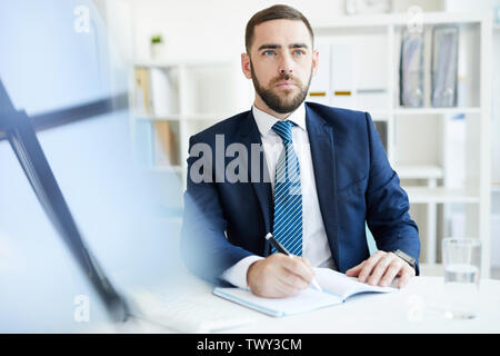 Serious purposeful young bearded businessman in formal suit sitting at table and making notes in diary while planning schedule - Stock Photo