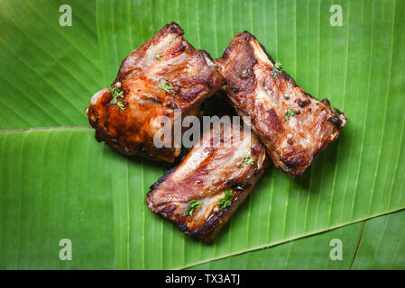 bbq pork ribs grilled with herbs spices served on banana leaf / Roasted barbecue pork spare rib sliced - Stock Photo